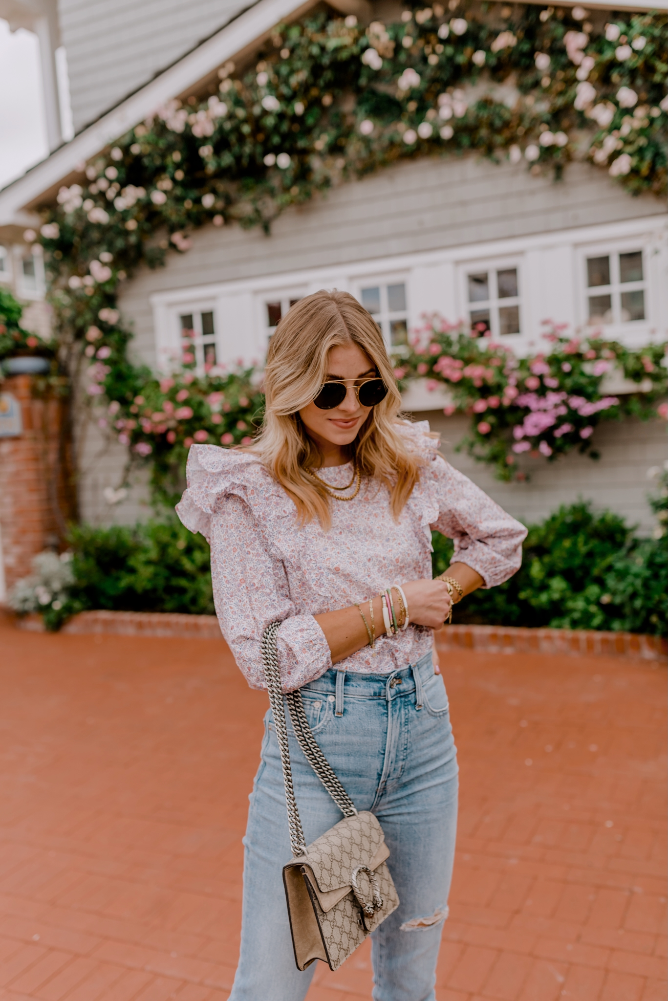 woman looking down and wearing ruffle top and jeans