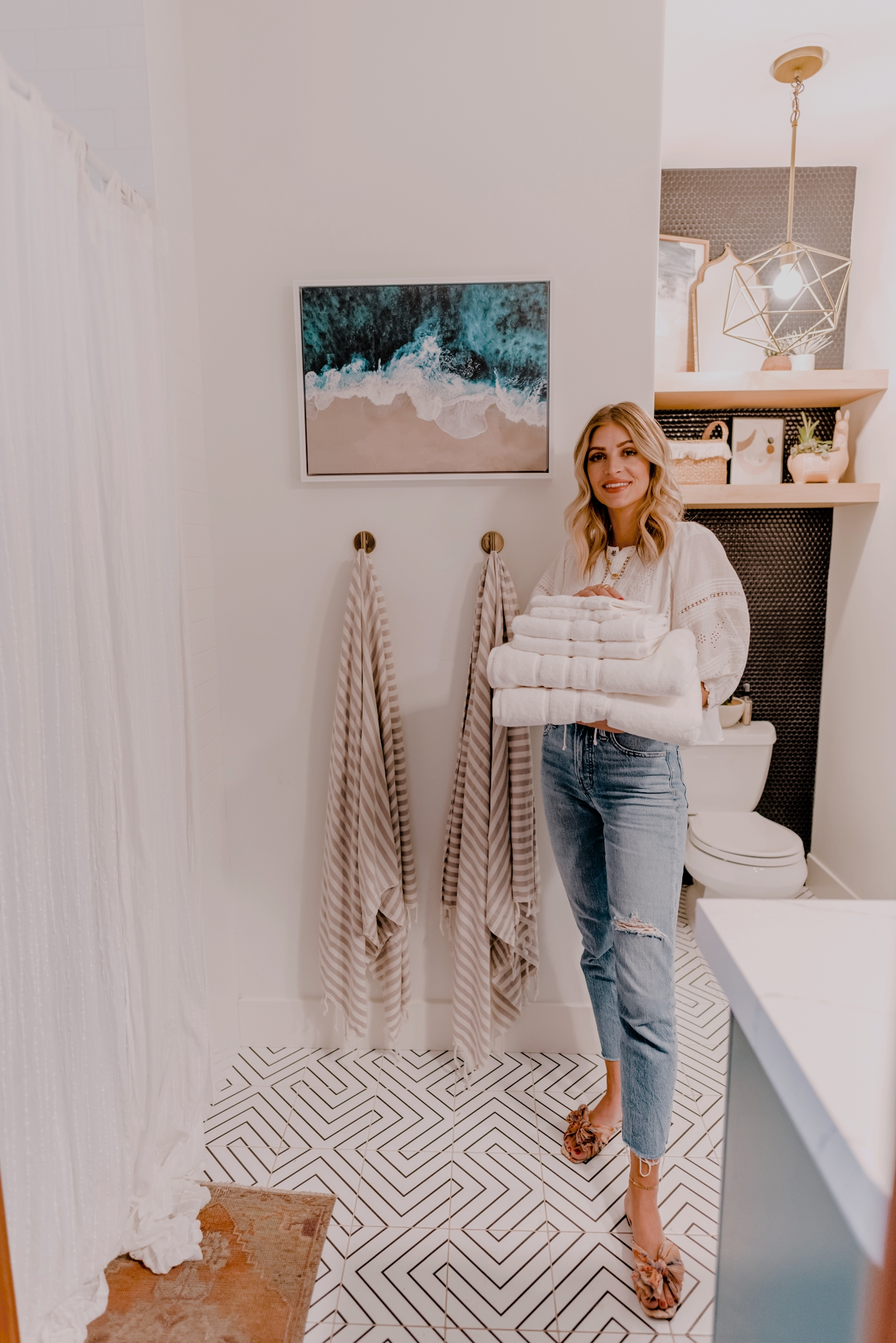 woman in the bathroom holding white towels and showing Decor Essentials for Hosting Guests