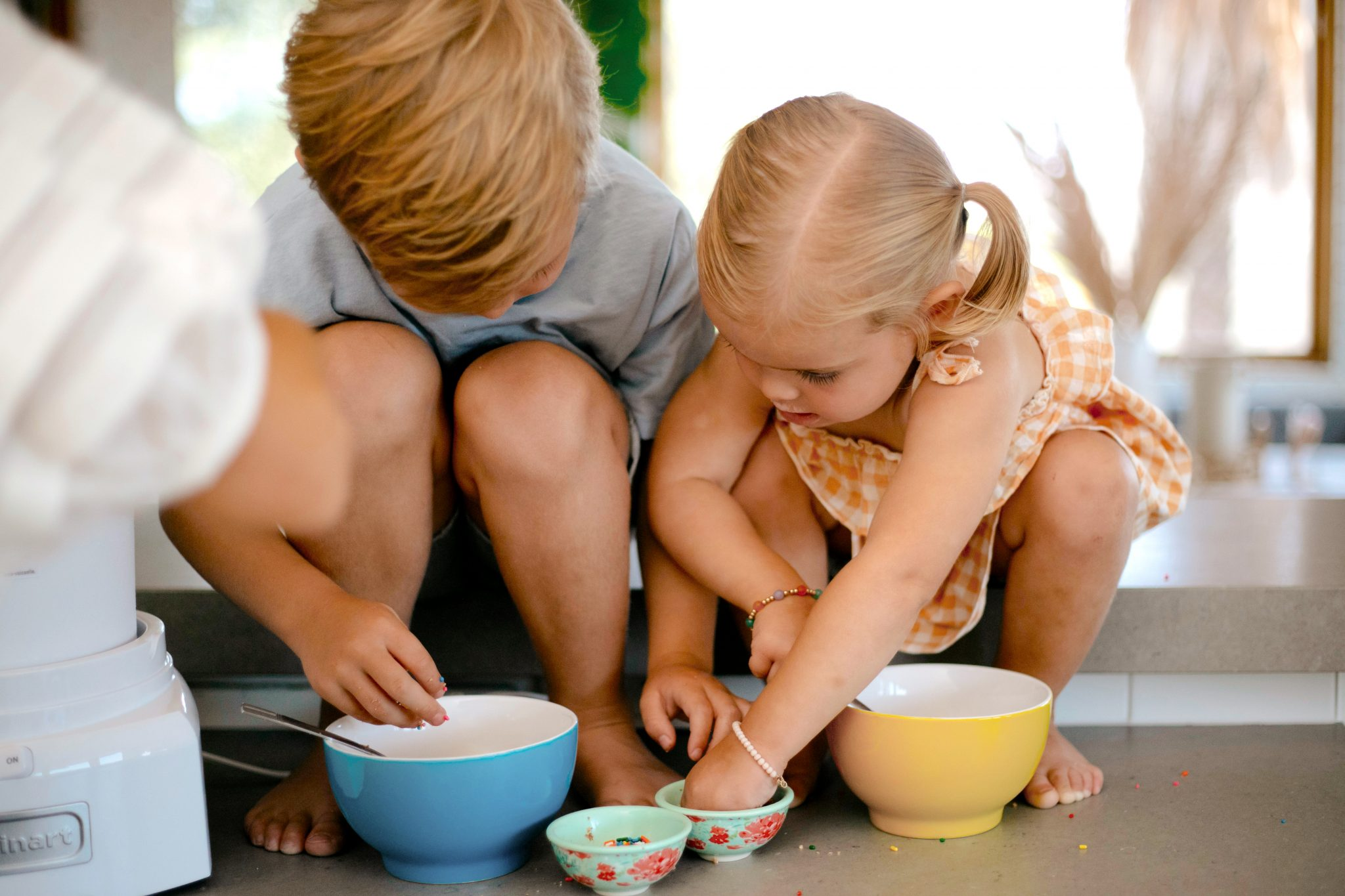 two kids playing with colorful bowls