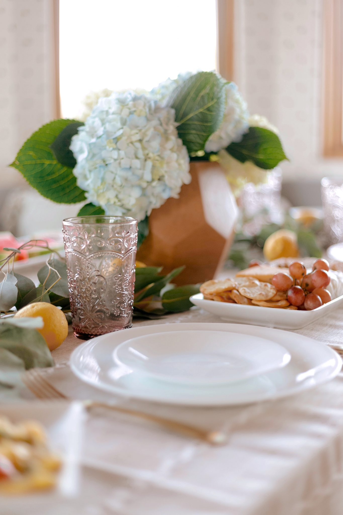 closeup of plates and food on table for hosting friends and family for dinner