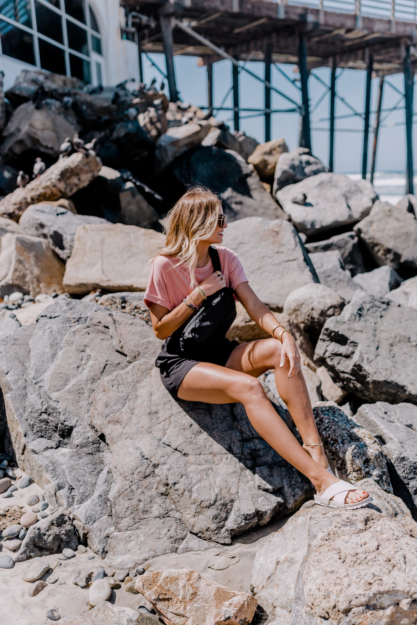 woman sitting on a rock at the beach