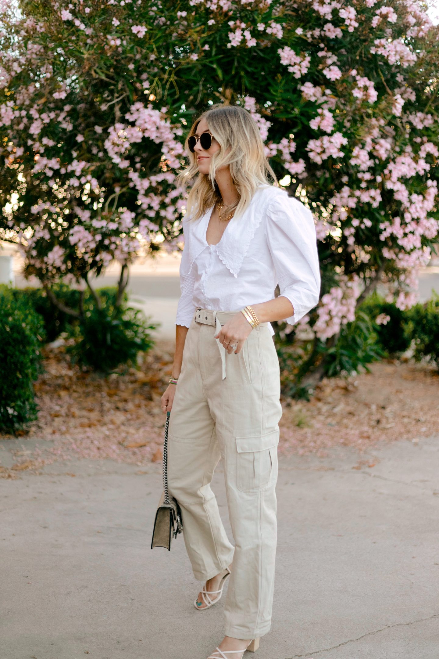 woman wearing cream pants and white button down top