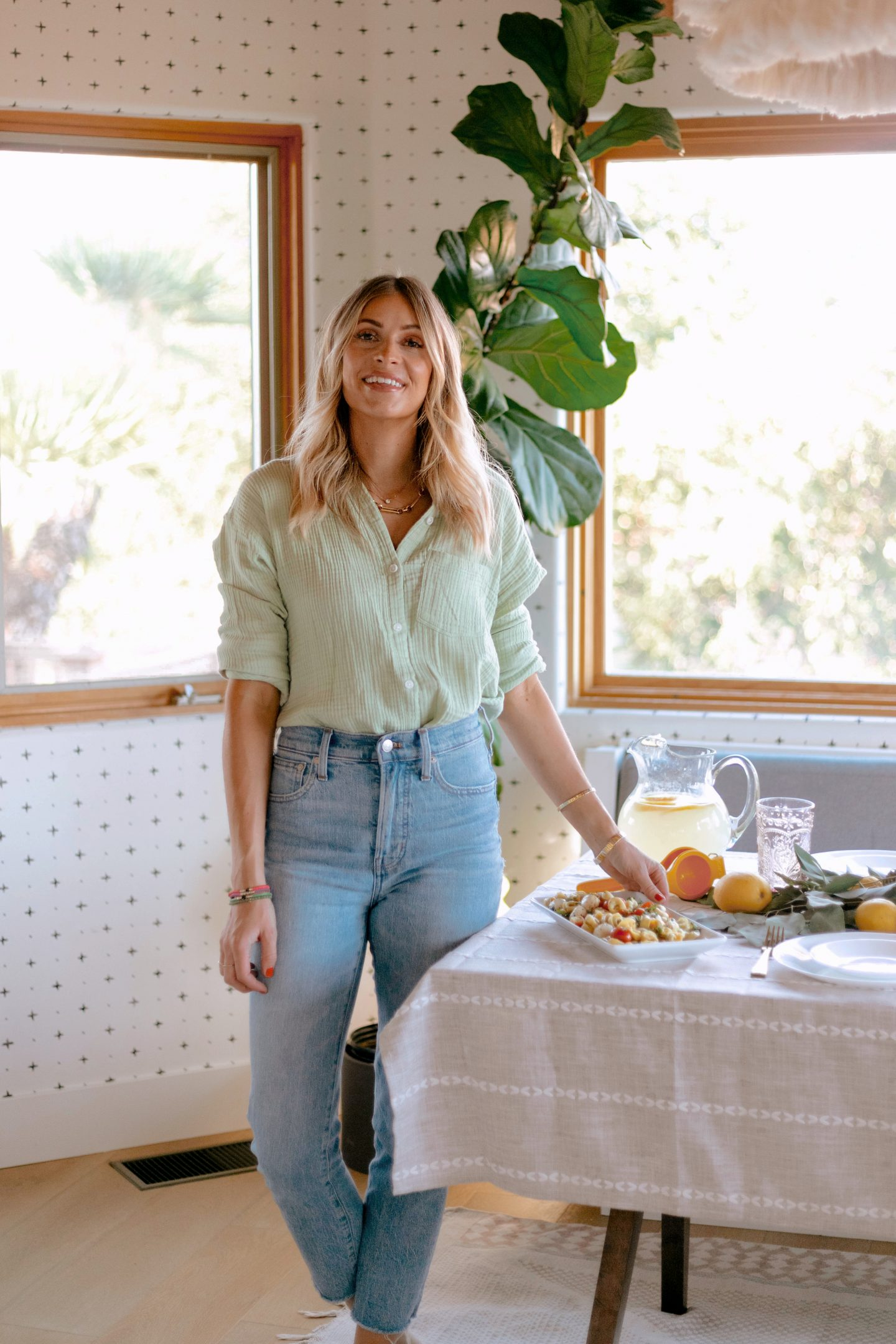 woman standing near a table for hosting friends and family for dinner