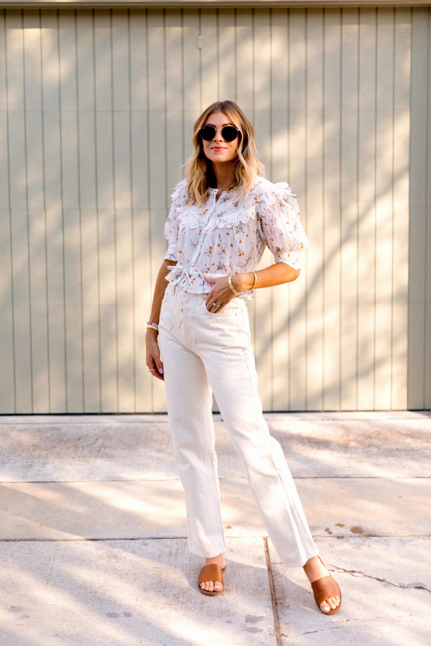 woman wearing white pants and printed top from august new arrivals