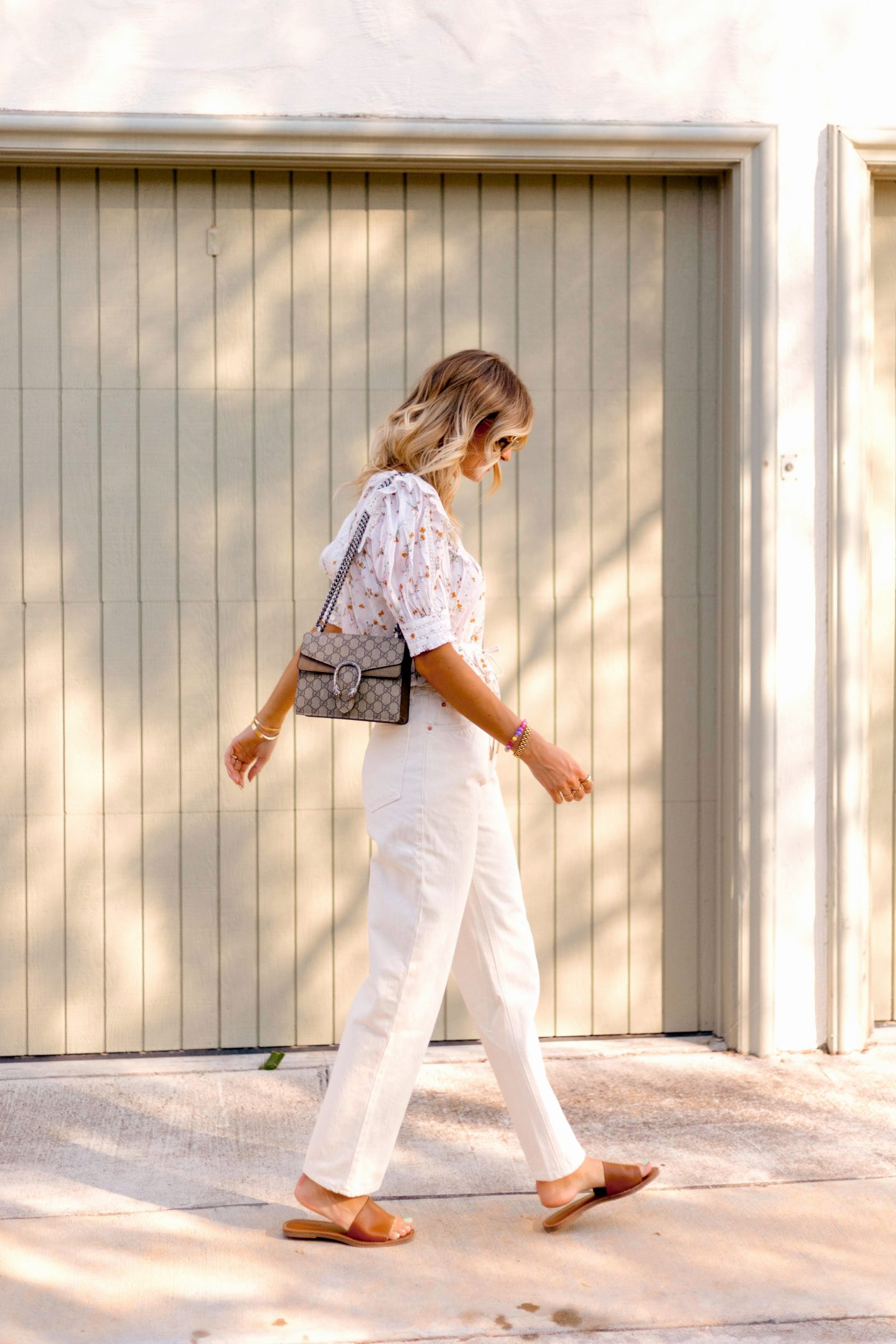 woman wearing printed top and white pants