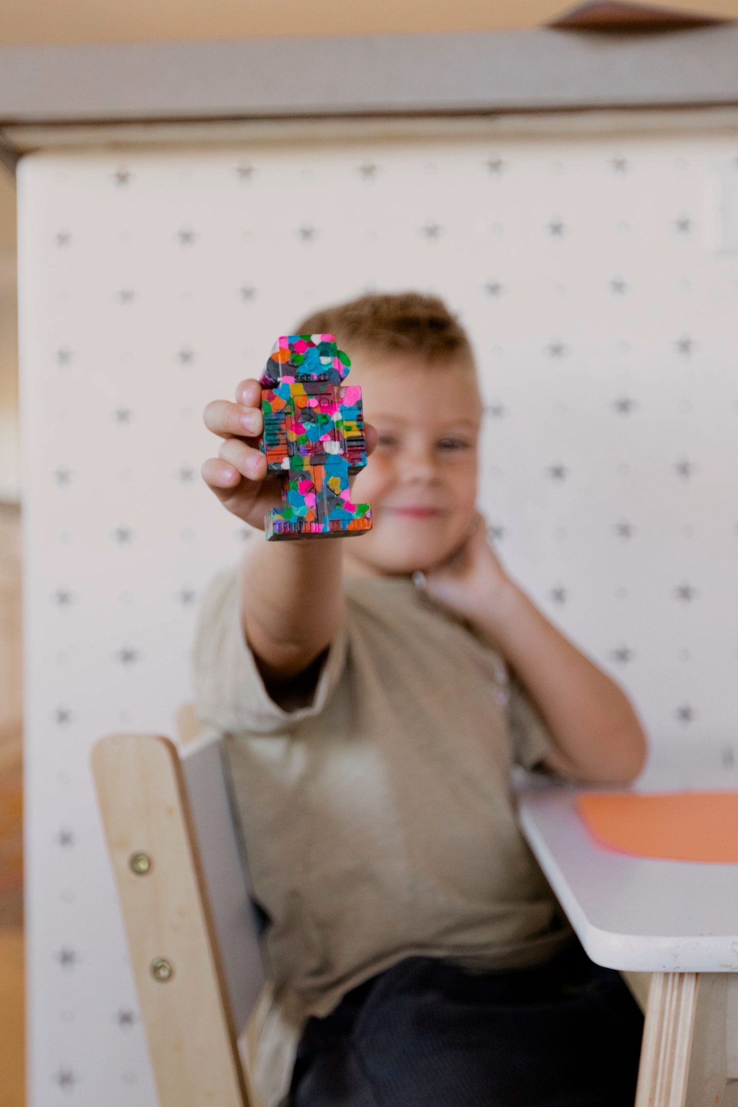kid holding a painted robot toy